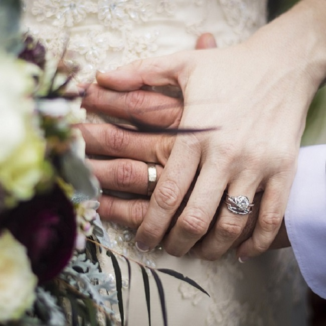 Bride and Groom holding hands showing off their engagement rings and wedding bands.