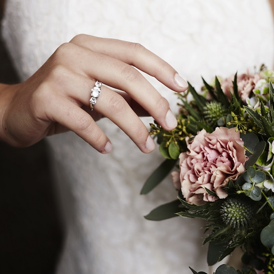 Bridge showing off her wedding band and engagement ring while holding a bouquet,