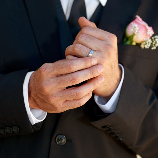 Groom showing off his wedding band dressed in wedding attire.